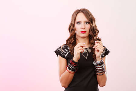 Pretty young woman wearing multiple bracelets jewellery necklace in black elegant evening dress on pink