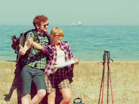 Adventure, summer, tourism. Young couple backpacker hitchhiker with map by seaside hitchhiking with thumb up gesture.