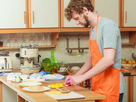 Young man in apron cooking preparing dinner food in kitchen. Stock Photo