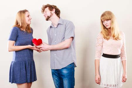 Los celos y el concepto de traición. Muchacha abandonada sin amor viendo en abrazándose feliz pareja. Relación Triángulo.