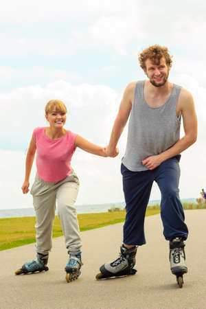 Vacaciones activas, ejercicios, concepto de relación. joven vestido con ropa deportiva poniendo a su novia hasta qué patinar mientras mantiene su mano en el paseo Foto de archivo