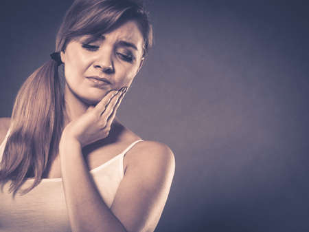 Dental care and toothache. Young woman achy girl suffering from terrible tooth pain, touching pressing her cheek by hand palm. Stock Photo