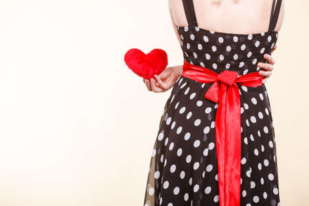 Valentine day gift, proof of love, romantic present concept. Woman in retro polka dot dress holding small furry red heart Stock Photo