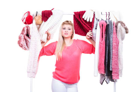 winter fashion: Young woman indecision in wardrobe home closet, teen blonde girl choosing her warm fashion outfit on clothing rack. Picking winter autumn clothes, shopping concept. Stock Photo