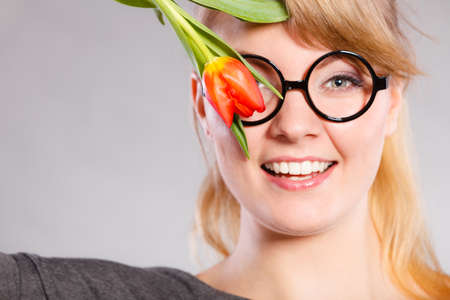 tenderly: Fun casual flora nature beauty feminine concept. Cheerful girl with flower. Smiling lady in glasses holding tulip to her face.