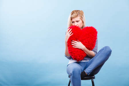 Break up, divorce, bad relationship concept. Sad, depressed woman holding big red fluffy pillow in heart shape, she needs love.
