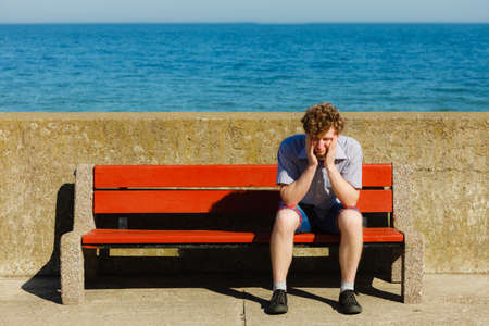 Tired exhausted man sitting on bench by sea ocean. Young guy relaxing outdoor. Summer vacation. Stock Photo