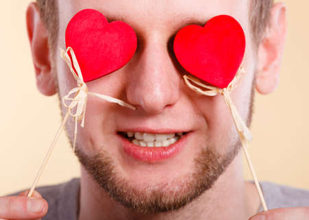 blinded: Love romance concept. Man blinded by love. Young male holding hearts on sticks before his eyes.