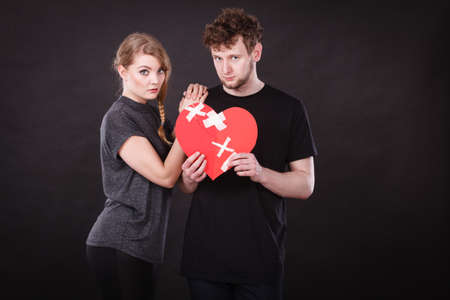 pain: Broken heart difficult love concept. Sad unhappy couple woman and man holding paper red heart fixed with plaster bandage. Rift in relations.