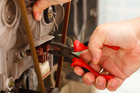 Domestic mechanical industrial concept. Mechanic repairing washing machine. Person using tools to fix broken device. Stock Photo