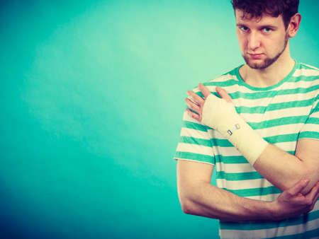 pain: Pain and injury concept. Young man holds bandaged hand. Injured part of body. Medicine and healthcare.