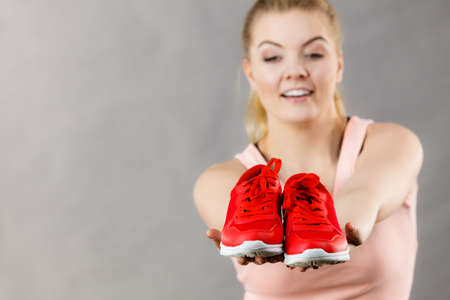 athletic wear: Happy sporty smiling woman presenting sportswear trainers red shoes, comfortable footwear perfect for workout and training.
