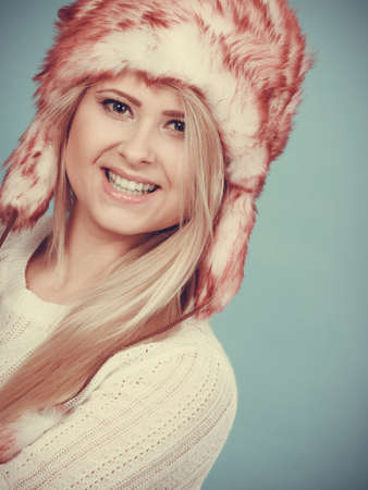 winter fashion: Accessories and clothes for cold days, fashion concept. Happy blonde woman in winter warm furry hat in russian style