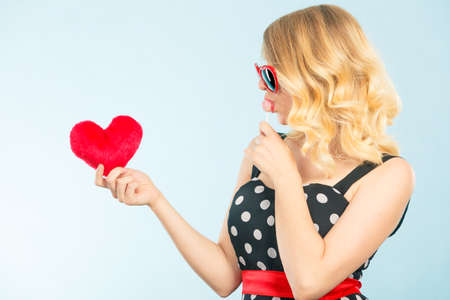 Woman blonde lovely girl wearing dotted dress holding red heart love symbol and lollipop candy. Valentines day, happiness, sweet food concept