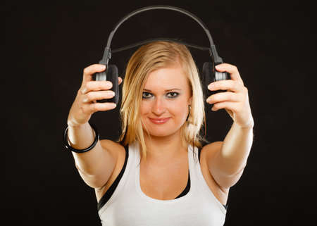 Music, passion concept. Studio shot of blonde young woman holding big headphones in front of face,