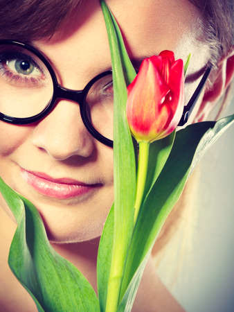 tenderly: Fun casual flora nature beauty feminine concept. Cheerful girl with flower. Attractive lady in glasses holding tulip to her face.