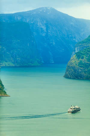 Tourism and travel. Mountains landscape and cruise liner ship sailing on the fjord, Norway Scandinavia.