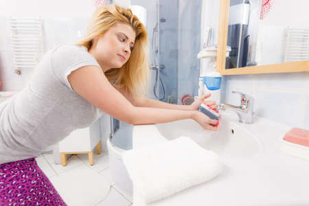 Woman washing her hands in sink to get rid of dirt using brush. Personal hygiene concept.