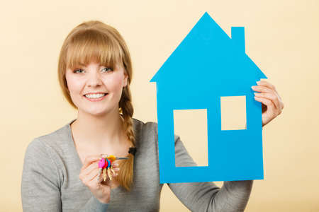 Ownership and property concept. Young blonde smiling female owner with bunch of colorful keys and house. Woman with key antry to her first own flat.