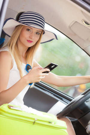 careless: Distracted driver. Young attractive woman using mobile phone, texting or read message while driving the car.