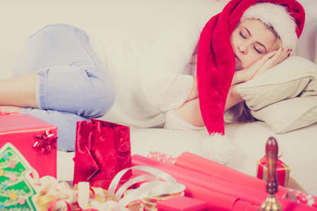 Christmas expectation, leisure and relaxation concept. Woman in Santa hat sleeping on couch waiting for gifts.