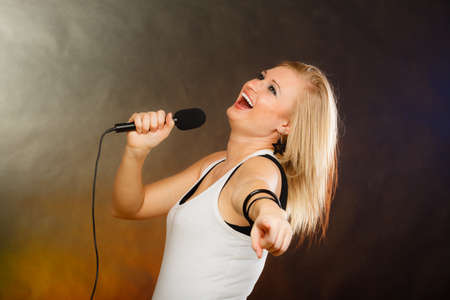 Karaoke, music, singer concept. Portrait of blonde woman singing to microphone, young star performing having fun, studio shot.