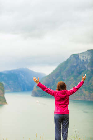 Travel concept. Happy free tourist woman in happiness and elated enjoyment with arms raised outstretched up looking at fjords mountains in Norway