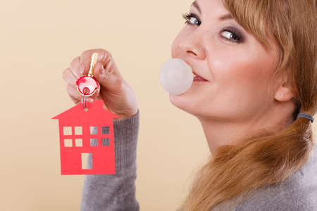 real estate sold: Young happy woman doing bubble with chewing gum while holding new house key with red home shape. Real estate housing and happiness concept. Stock Photo