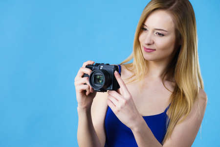 Young woman holding old fashioned analog camera taking pictures. Studio shot on blue background.