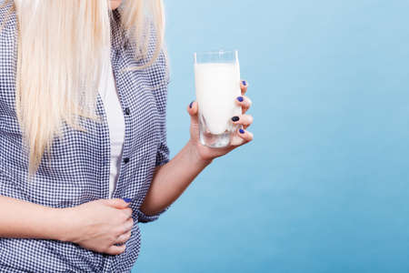 Lactose intolerance, health problem with dairy food products concept. Woman holding glass of milk having bad stomach ache. Banque d'images