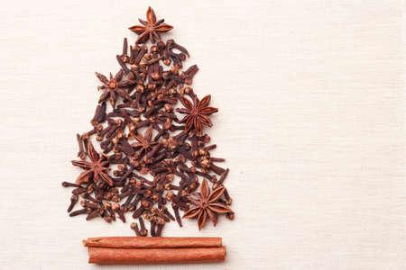 Albero di Natale fatto dalle stelle e dai chiodi di garofano dell'anice del bastone di cannella delle spezie marroni sul fondo della tela da imballaggio Archivio Fotografico