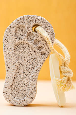 Feet care. Pedicure accessory tool: stone pumice with foot print and bar of soap closeup Stock Photo