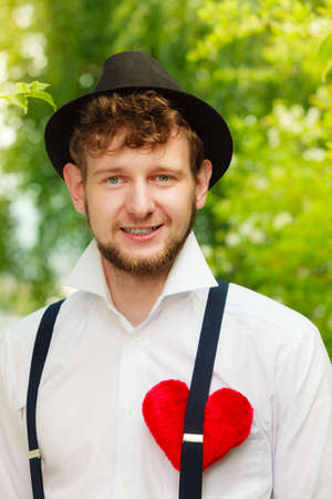 amish: Love concept. Young fashionable man in hat retro style with red heart on chest