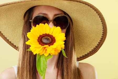 Closeup of attractive summer woman in sunglasses straw hat with sunflower in her hand on yellow background Stock Photo
