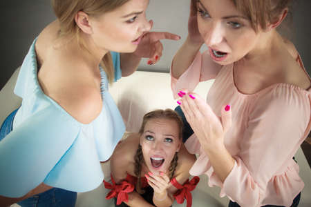 Woman being gossiped bullied by two female friends. Friendship difficulties, rivaly and envy problems.