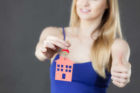 real estate sold: Young woman holding new house key with red home shape, giving thumb up. Real estate and housing concept. Stock Photo