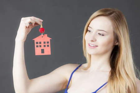 owning: Young woman holding new house key with red home shape. Real estate and housing concept. Stock Photo