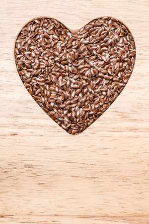Diet healthcare healthy food. Raw flax seeds linseed heart shaped on wooden board background. Imagens