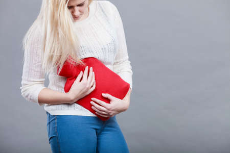 Painful periods and menstrual cramp problems concept. Woman having stomach cramps feeling very unwell holding hot water bottle.