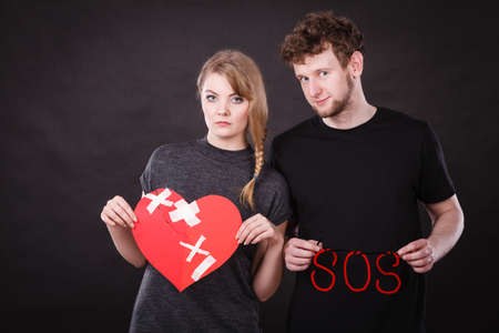 Betrayal and break up in relationship. Young couple with big plaster broken heart and red sos word sign symbol. Negative emotions.
