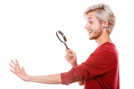 absorption: Narcissist, self absorption concept. Male holding magnifying glass looking at hands fingers nails obsessing about cleanliness, isolated on white