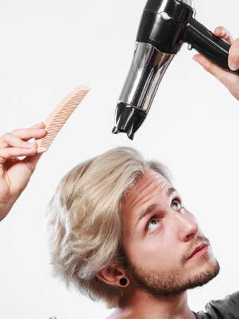 dryer: Hairstyle and fashion. Young trendy male hairstylist barber with new idea of look changing. Blonde man holding hair dryer and comb creating new hairdo