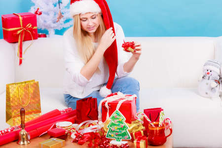 Holiday gifts, seasonal concept. Woman in Santa hat sitting on sofa preparing and packing christmas presents