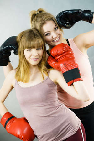 Friendship, human relations concept. Two happy women friends having fun smiling with joy wearing boxing gloves being fit and sporty.