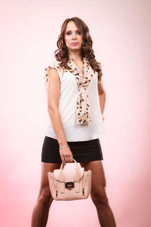 Elegant outfit. Female fashion. Girl in fashionable clothes holding bag handbag studio shot on pink background