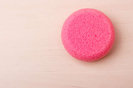 smoothen: Foot care pedicure. Pink pumice stone on wooden surface