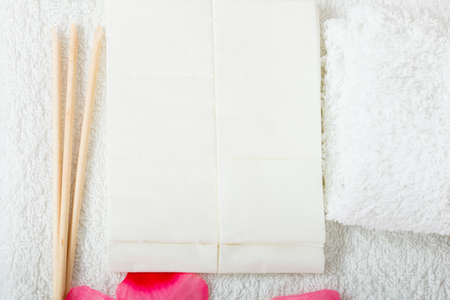 Manicurist set, cuticles wooden sticks pusher and white files on towel with rose petals.