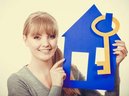 Selling and buying real estate concept. Young blonde smiling positive female estate agent ready to sell house home. Stock Photo