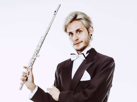 Classical music study concept. Male flutist musician performer playing flute. Young elegant man wearing tailcoat holds instrument Stock Photo