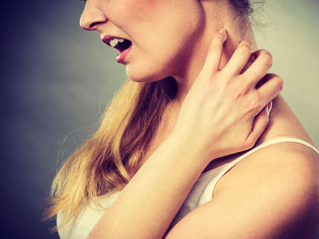 Health problem, skin diseases. Young woman scratching her itchy neck with allergy rash